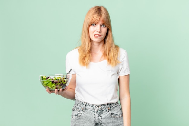 Mooie roodharige vrouw die verbaasd en verward kijkt en een salade vasthoudt. dieet concept