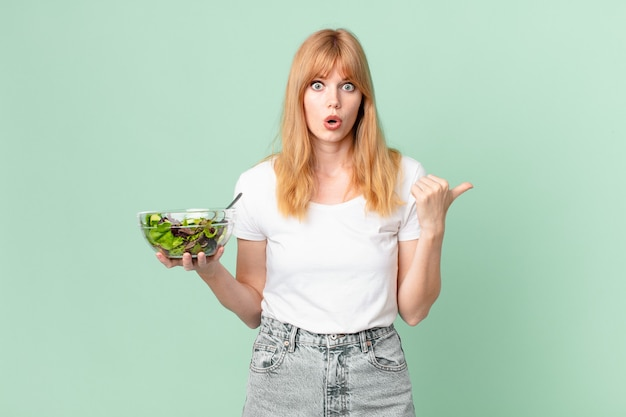 Mooie roodharige vrouw die verbaasd kijkt in ongeloof en een salade vasthoudt. dieet concept