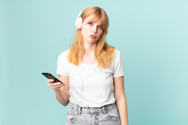 Mooie roodharige vrouw die verdrietig en zeurt met een ongelukkige blik en huilt en luistert naar muziek met een koptelefoon