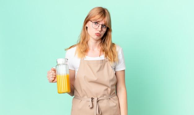 Mooie roodharige vrouw die verdrietig en zeurt met een ongelukkige blik en huilt met een schort die een sinaasappelsap bereidt