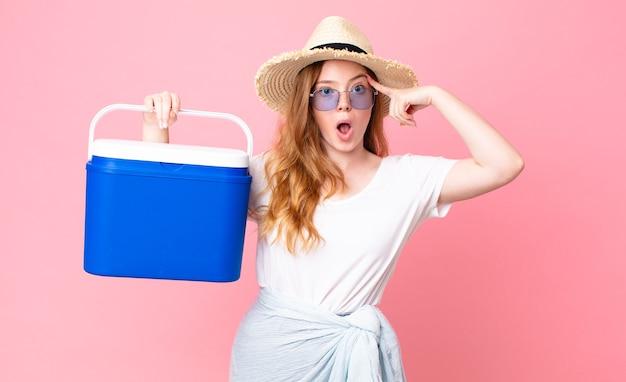 Mooie roodharige vrouw die verrast kijkt, een nieuwe gedachte, idee of concept realiseert en een draagbare picknickkoelkast vasthoudt