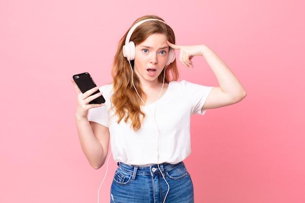 Mooie roodharige vrouw die verrast kijkt en een nieuwe gedachte, idee of concept realiseert met koptelefoon en smartphone