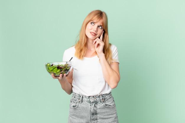 Mooie roodharige vrouw die vrolijk lacht en dagdroomt of twijfelt en een salade vasthoudt. dieet concept