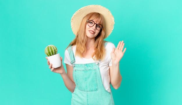 Mooie roodharige vrouw die vrolijk lacht, met de hand zwaait, je verwelkomt en begroet en een ingemaakte cactus vasthoudt. boer concept