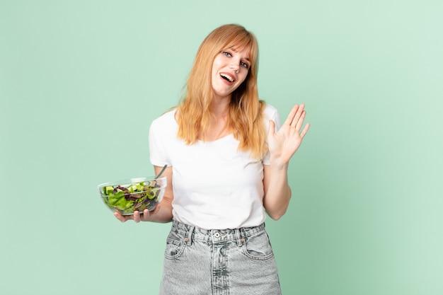 Mooie roodharige vrouw die vrolijk lacht, met de hand zwaait, je verwelkomt en begroet en een salade vasthoudt. dieet concept