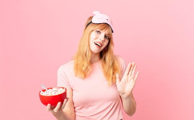 Mooie roodharige vrouw die vrolijk lacht, met de hand zwaait, je verwelkomt en begroet in een pyjama en een vlokkenkom vasthoudt
