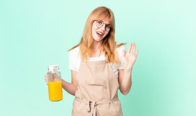 Mooie roodharige vrouw die vrolijk lacht, met de hand zwaait, je verwelkomt en begroet met een schort dat een sinaasappelsap bereidt