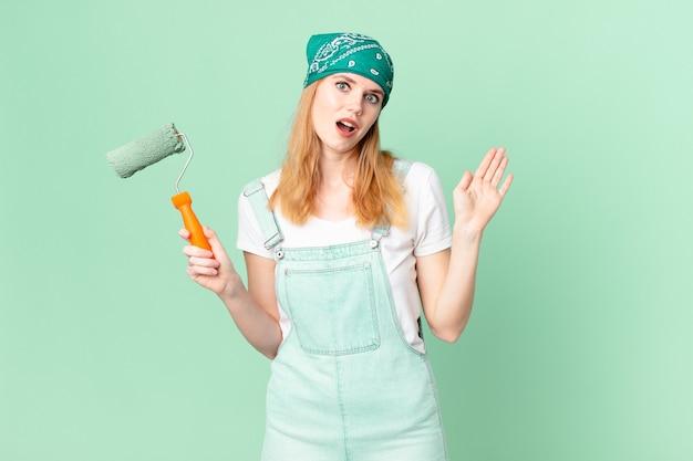 Mooie roodharige vrouw die vrolijk lacht, met de hand zwaait, je verwelkomt en begroet met het schilderen van huisconcept
