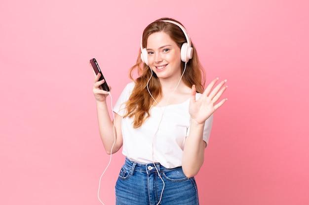 Mooie roodharige vrouw die vrolijk lacht, met de hand zwaait, je verwelkomt en begroet met koptelefoon en smartphone
