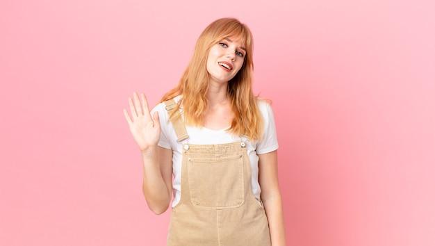 Mooie roodharige vrouw die vrolijk lacht, met de hand zwaait, je verwelkomt en begroet