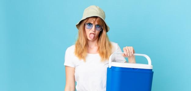 Mooie roodharige vrouw die walgt en geïrriteerd voelt en tong uitsteekt en een draagbare koelkast vasthoudt. zomer concept