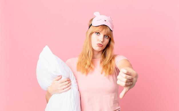 Mooie roodharige vrouw die zich boos voelt en duimen naar beneden laat zien. een pyjama dragen en een kussen vasthouden
