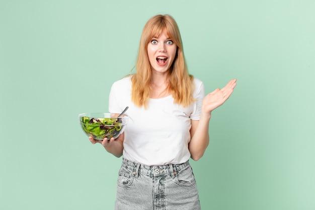 Mooie roodharige vrouw die zich gelukkig en verbaasd voelt over iets ongelooflijks en een salade vasthoudt. dieet concept