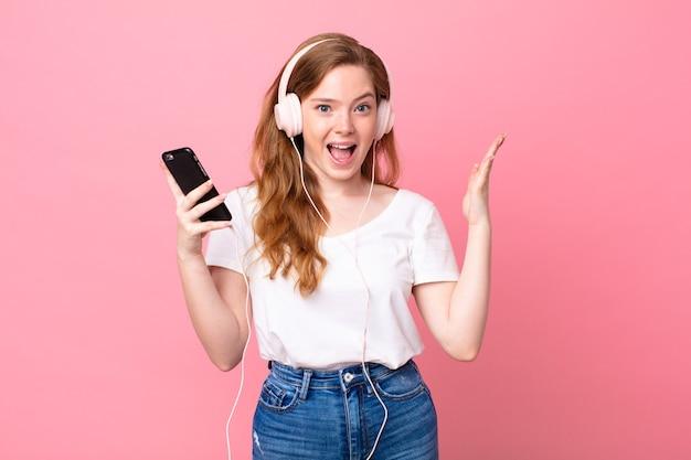 Mooie roodharige vrouw die zich gelukkig en verbaasd voelt over iets ongelooflijks met koptelefoon en smartphone