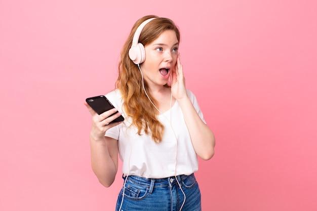Mooie roodharige vrouw die zich gelukkig, opgewonden en verrast voelt met koptelefoon en smartphone
