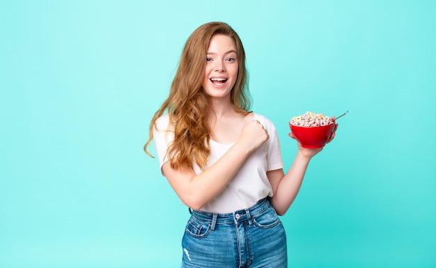 Mooie roodharige vrouw die zich gelukkig voelt en een uitdaging aangaat of een ontbijtkom viert en vasthoudt