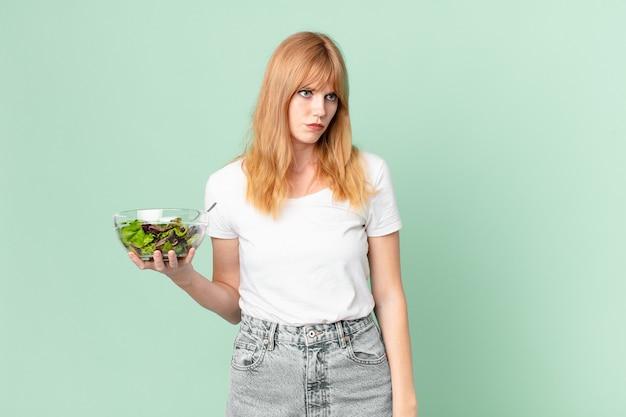 Mooie roodharige vrouw die zich verdrietig, overstuur of boos voelt en naar de zijkant kijkt en een salade vasthoudt. dieet concept