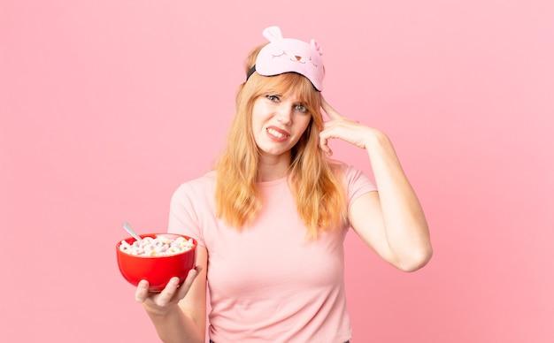 Mooie roodharige vrouw die zich verward en verbaasd voelt en laat zien dat je gek bent als je een pyjama draagt en een vlokkenkom vasthoudt