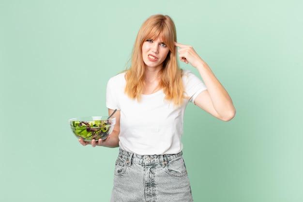 Mooie roodharige vrouw die zich verward en verbaasd voelt, laat zien dat je gek bent en een salade vasthoudt. dieet concept