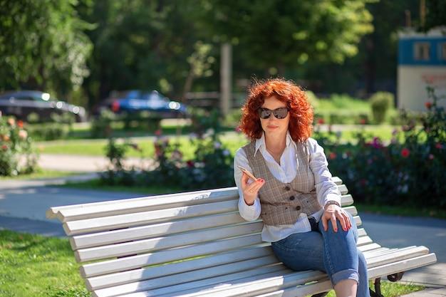 Mooie roodharige vrouw in de zomer zit op een bankje in het park en maakt gebruik van de telefoon