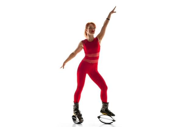 Mooie roodharige vrouw in een rode sportkleding springen in een kangoo springt schoenen geïsoleerd op een witte studio achtergrond. hoog springen, actief bewegen, actie, fitness en wellness. passend vrouwelijk model.