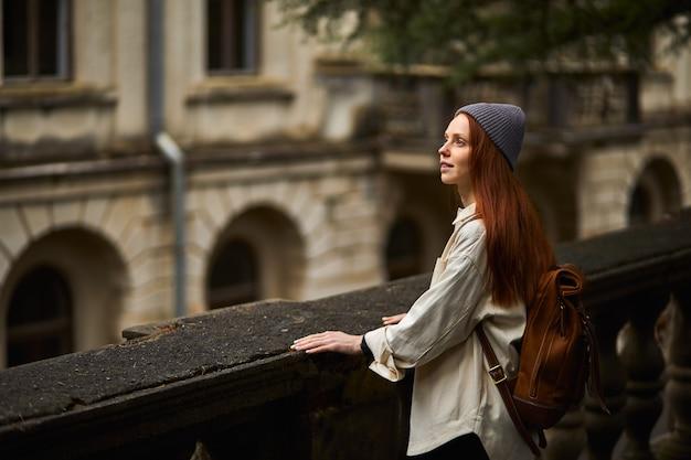 Mooie roodharige vrouw in jas op zoek naar prachtige historische plek rondkijken staan in contempl...