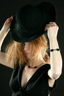 Mooie roodharige vrouw in zwart, hoed en juwelen