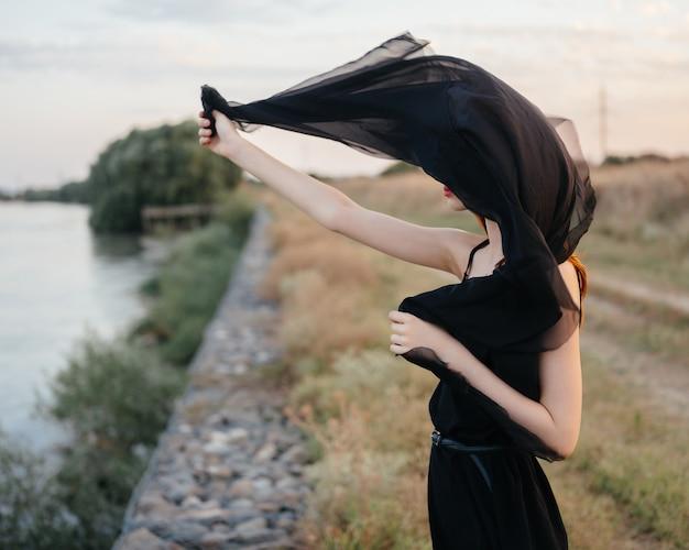 Mooie roodharige vrouw in zwarte jurk buitenshuis poseren in de frisse lucht
