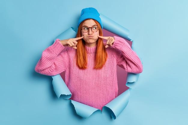 Mooie roodharige vrouw maakt grappige grimas klappen wangen en punten met wijsvingers houdt de adem in draagt blauwe hoed gebreide trui.