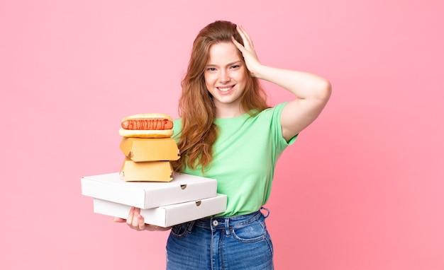 Mooie roodharige vrouw met afhaalmaaltijden voor fastfood