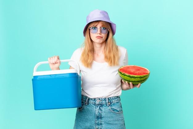 Mooie roodharige vrouw met een draagbare koelkast en een watermeloen
