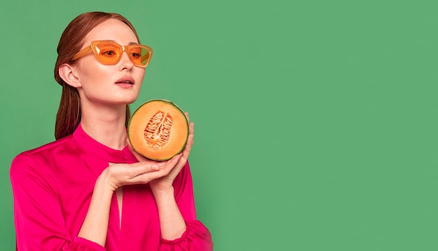 Mooie roodharige vrouw met een meloen met kopie ruimte