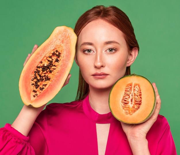 Mooie roodharige vrouw met een meloen