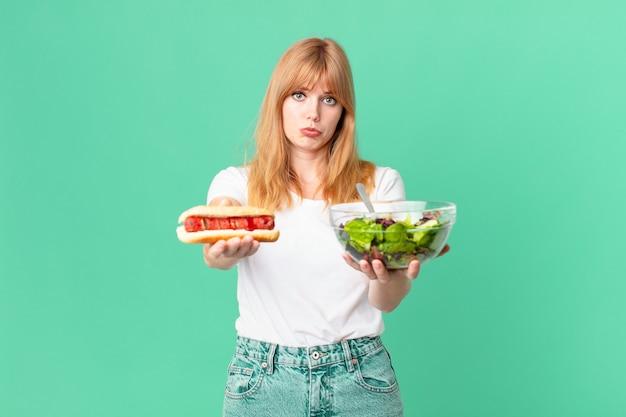 Mooie roodharige vrouw met een salade en een hotdog. dieet concept