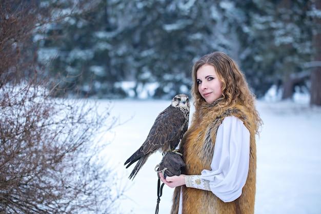 Mooie roodharige vrouw met een valk in de winter