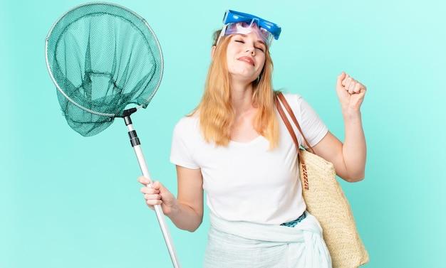 Mooie roodharige vrouw met een vissersnet en een bril.