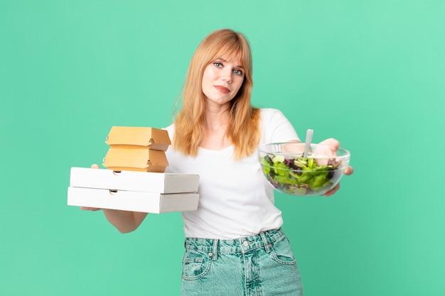 Mooie roodharige vrouw met fastfooddozen en een salade