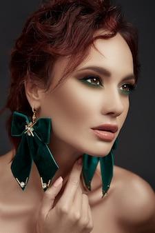 Mooie roodharige vrouw met make-up en groene oorbellen