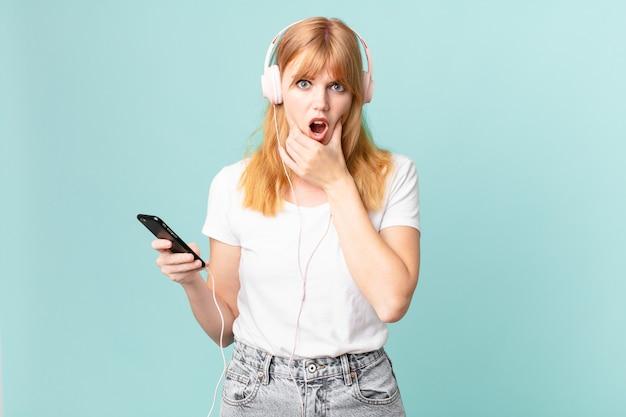 Mooie roodharige vrouw met mond en ogen wijd open en hand op kin en luisterende muziek met koptelefoon