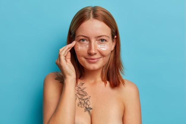 Mooie roodharige vrouw met schone, frisse, gladde huid, past hydrogel transparante pleisters toe, onder een huidverzorgingsmasker voor de ogen, geniet van collagente behandeling, staat shirtless, geïsoleerd op blauwe muur.