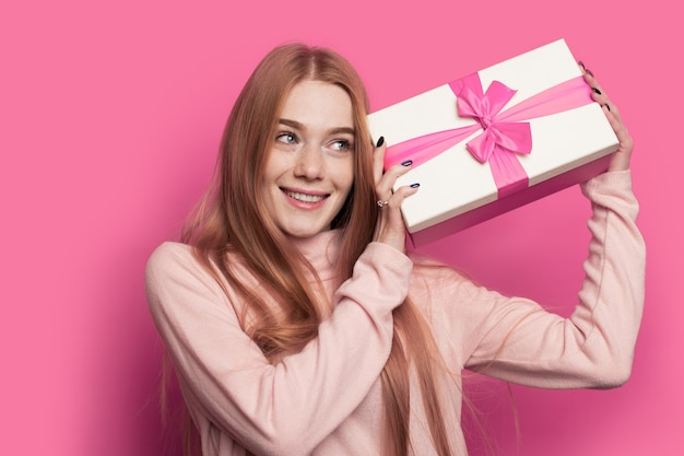 Mooie roodharige vrouw met sproeten en rood haar schudt een cadeau en glimlacht op een roze studiomuur