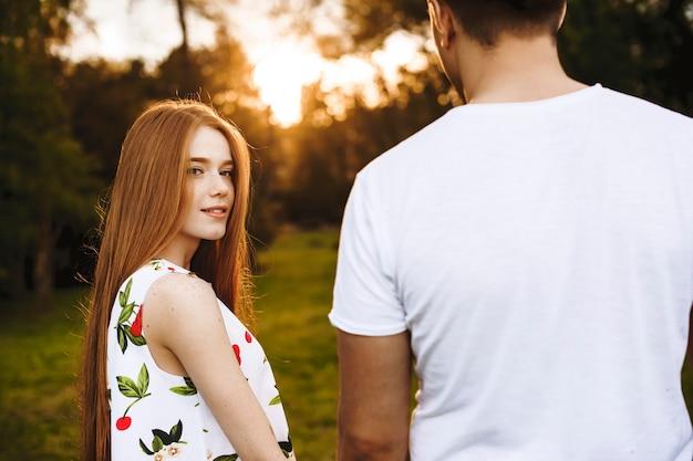 Mooie roodharige vrouw met sproeten kijken camera glimlachen terwijl hand van haar vriendje tegen zonsondergang terwijl dating buiten in het park.