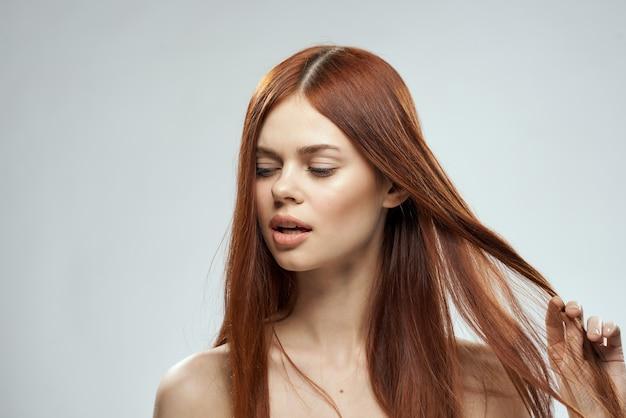 Mooie roodharige vrouw naakte schouders cosmetica lang haar glamour lichte muur.