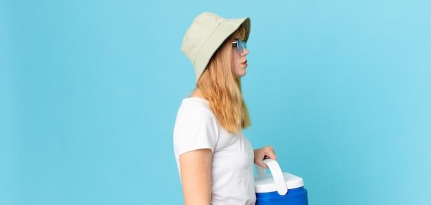 Mooie roodharige vrouw op profielweergave denken, verbeelden of dagdromen en een draagbare koelkast vasthouden. zomer concept