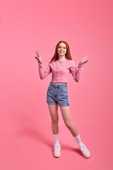 Mooie roodharige vrouw poseren, tonen v-teken geïsoleerd op levendige roze kleur achtergrond, studio portret. jonge vrouw in casual roze shirt en spijkerbroek ziet er gelukkig uit, in een goed humeur