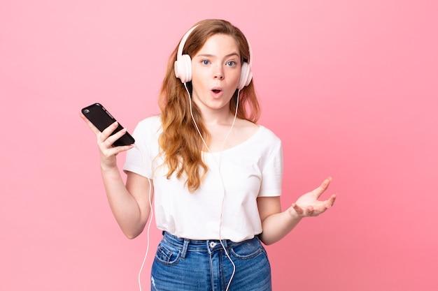 Mooie roodharige vrouw verbaasd, geschokt en verbaasd met een ongelooflijke verrassing met koptelefoon en smartphone