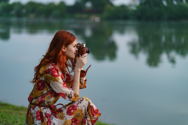 Mooie roodharige vrouwelijke fotograaf maakt foto's met een oude camera