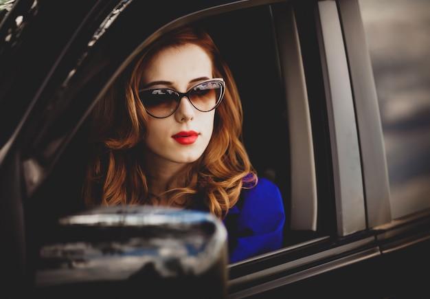 Mooie roodharigevrouw in de auto.
