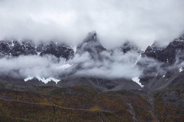 Mooie rotsachtige bergen gehuld in mist in de vroege ochtend