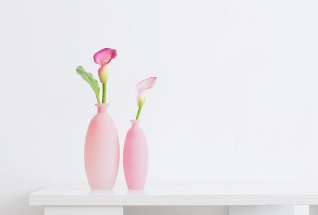 Mooie roze bloemen in vazen op wit